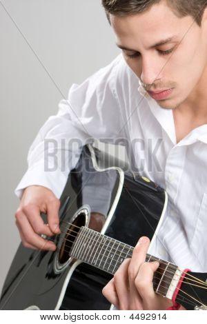Young Man Strums Acoustic Guitar
