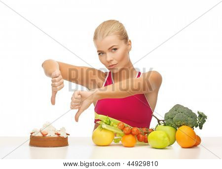 woman with healthy food showing thumbs down to cake