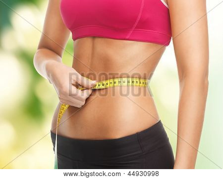 close up of trained belly with measuring tape