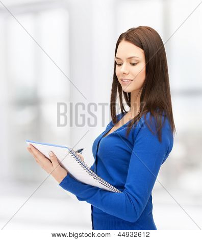 picture of smiling young businesswoman taking notes