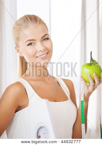 beautiful sporty woman with scale, green apple and measuring tape