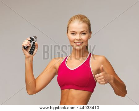 beautiful sporty woman with hand expander showing thumbs up