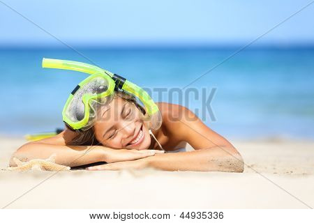 Travel summer vacation beach woman with snorkel. Smiling beautiful young woman relaxing lying on white beach sand in the summer sun with a blue ocean. Photo from Hapuna beach, Big Island, Hawaii, USA.