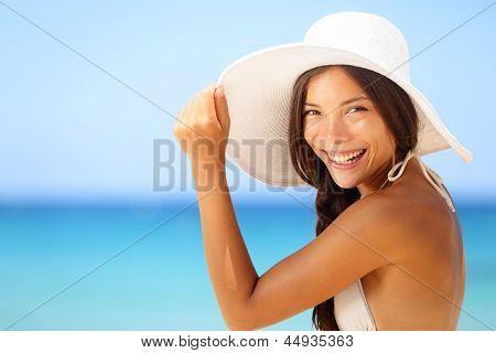 Vacation beach woman smiling happy portrait. Asian bikini girl on tropical beach wearing sun hat looking at camera happy. Summer lifestyle photo with mixed race Asian Caucasian female model.