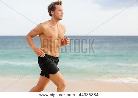 Sport man running. Male athlete runner jogging shirtless training on beautiful beach. Fit handsome male fitness model jogging alone training for marathon run. Caucasian man in his twenties.