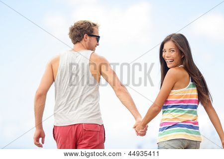 Happy cheerful young trendy couple holding hands walking together outside smiling having fun being in love. Beautiful young multiethnic couple, Asian woman, Caucasian man.