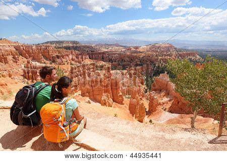 Hikers in Bryce Canyon resting enjoying view Hiking couple in beautiful nature landscape with hoodoos, pinnacles and spires rock formations. Bryce Canyon National Park, Utah, USA in summer.