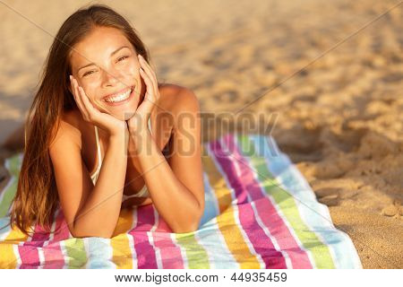 Beautiful woman sunbathing on the beach lying on a towel facing the camera with her chin cupped in her hands and a lovely vivacious smile on her face. Multicultural candid girl outside.