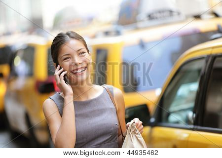 Business woman on smart phone in New York City, Manhattan walking in dress suit holding doggy bag smiling and laughing, Young multiracial Asian Caucasian professional female businesswoman in her 20s.