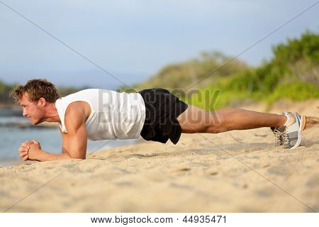 Crossfit training fitness man doing plank core exercise working out his midsection core muscles. Fit male fitness instructor planking exercising outside in summer on beach.
