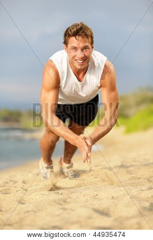 Push ups - crossfit fitness man doing clapping push-ups during training exercise workout on beach in summer. Fit male trainer and fitness model exercising intensely outside showing strength and power.