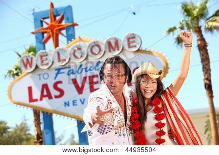 Las Vegas Elvis impersonator having fun cheering by Welcome to Fabulous Las Vegas sign. Funny happy joyful image with Elvis and smiling happy beautiful girl wearing cowboy hat on the Strip