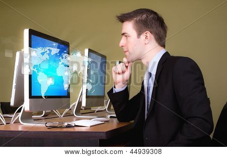 Portrait of young business man working in computer room with social network on world map