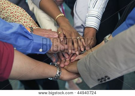Hands of businesspeople in huddle