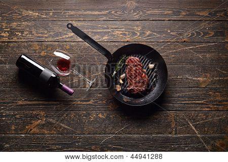 Em mármore bife de carne em uma panela de grelhar com uma garrafa de vinho e vidro com fundo de madeira velho. Suculenta