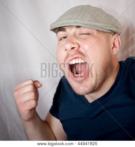 The serious young man shakes a fist