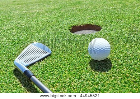 Golf Stick And Ball On The Grass Near The Hole.