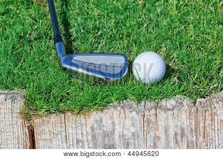Golf Ball And Stick Inverted Wooden Support On The Grass.