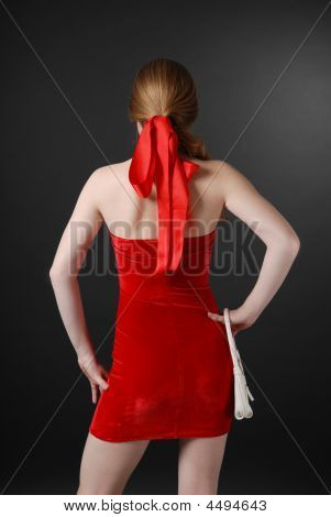 Girl In Red On Dark Background, Rear View