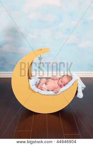 Beautiful Little Newborn baby boy in moon prop