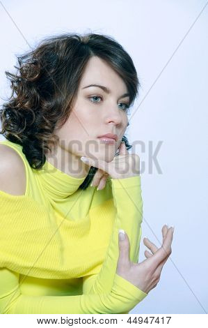 portrait in studio of a young caucasian  woman thinking serious on blue background  a yellow pull over