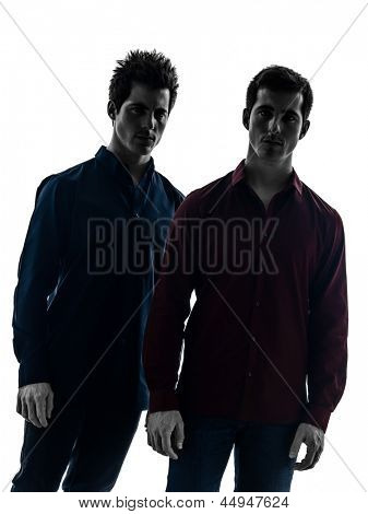 two caucasian young men standing serious in shadow  white background