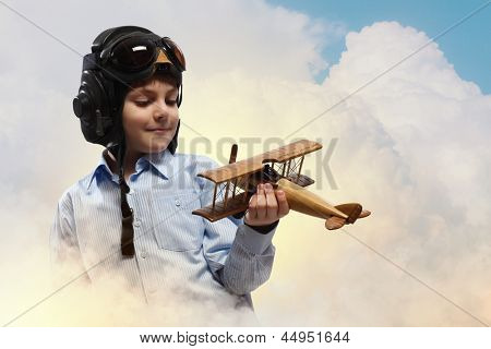 Image of little boy in pilots helmet playing with toy airplane against clouds background
