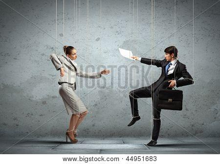 Imagen de empresarios en cadenas como marionetas. Fotografía conceptual