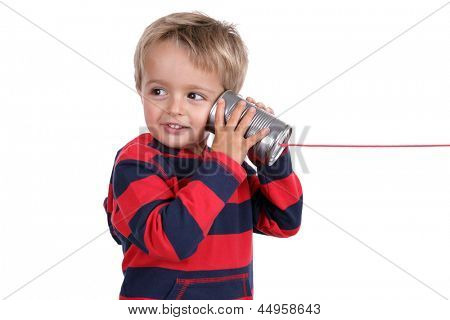 Little boy listening through a tin can phone connected by string, concept for communication