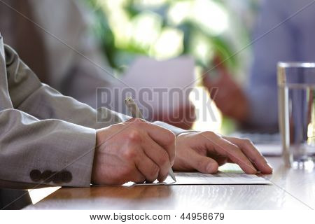 Business meeting or lecture with businessman writing or signing contract