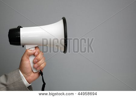 Businessman holding a megaphone in front of blank gray background ready for message