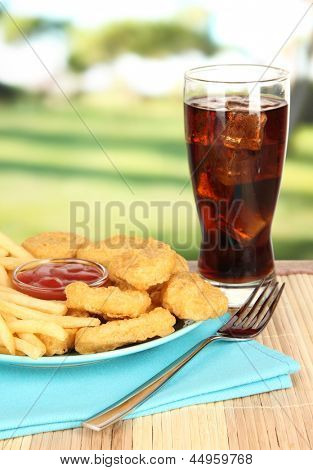Fried chicken nuggets with french fries,cola and sauce on table in park
