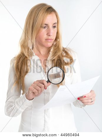 Woman inspecting closely a document through a magnifying glass