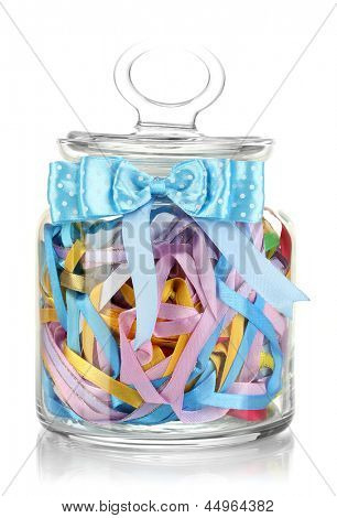 Glass jar containing various colored ribbons isolated on white