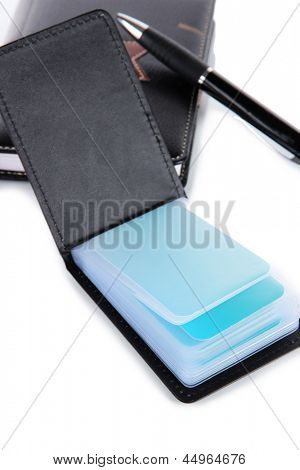 Black business card holder notebook and pen close-up