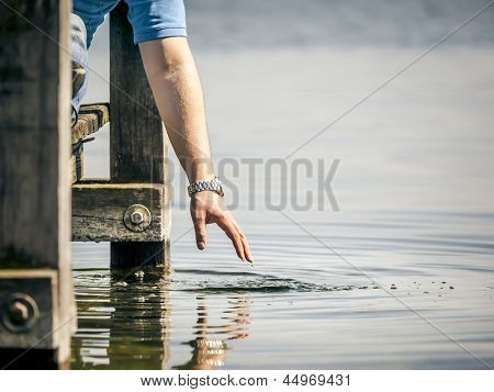 A man sitting on a wooden jetty and is playing with the water