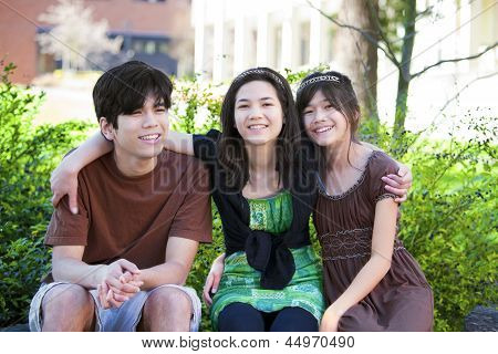 Three Brother And Sisters Sitting Outdoors On Log, Smiling