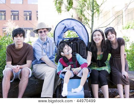 Father Sitting With His Biracial Children And Disabled Son