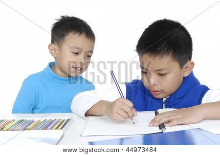 Two School boy sitting and writing in notebook. Isolated on white background