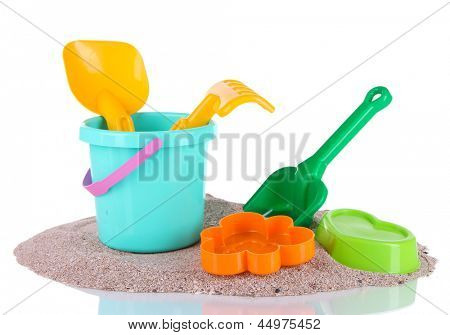 Children's toys on sand isolated on white