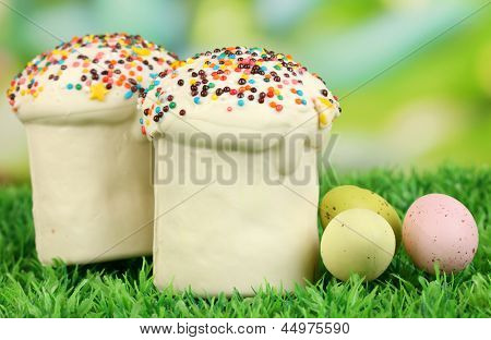 Easter cake with sugar glaze and eggs on grass