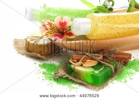 Bottles with scrub and hand-made soap, isolated on white