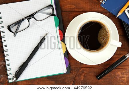 Cup of coffee on worktable covered with documents close up