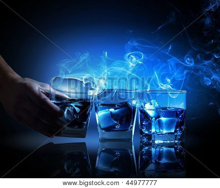Three glasses of blue cocktail with fume going out