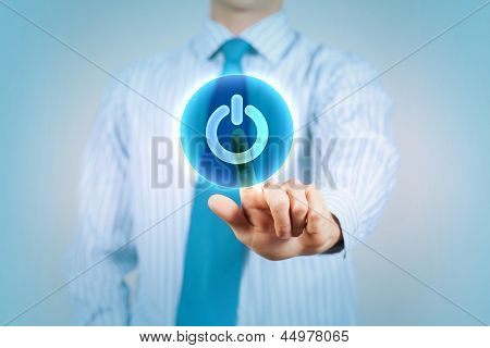 Young man in a light shirt and blue tie press the power button. Shallow depth of field.