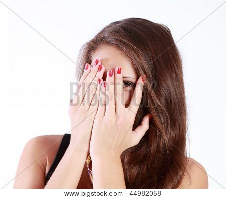 Young Woman Hides Her Face In Her Palms And Spies Isolated On White Background.