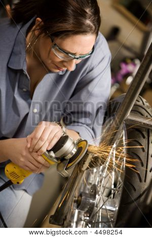 Hispaninc Womman Using Grinder On Motorcycle