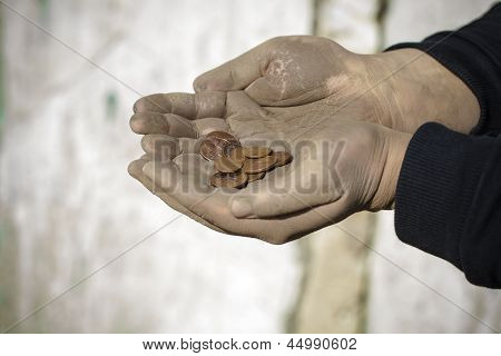 Dirty  hands with coins on a wall background