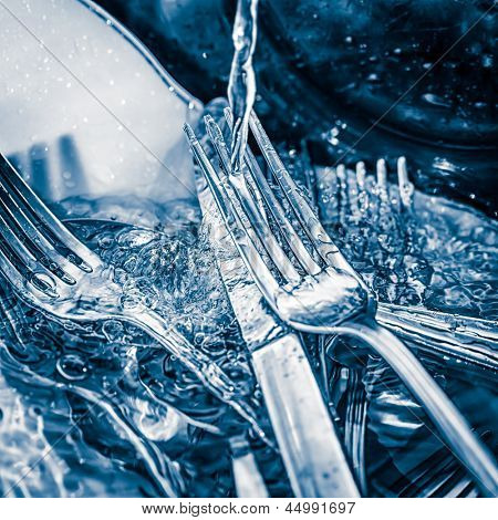 Blue toned image of forks and knives   washed on a sink with a splash of water