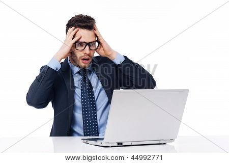 Shocked businessman looking at laptop